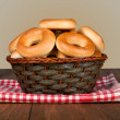 Stock Photo: Tasty bagels in basket on wooden background