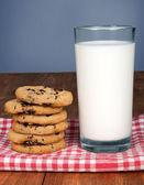 Glas melk en koekjes op houten tafel op bue achtergrond — Stockfoto