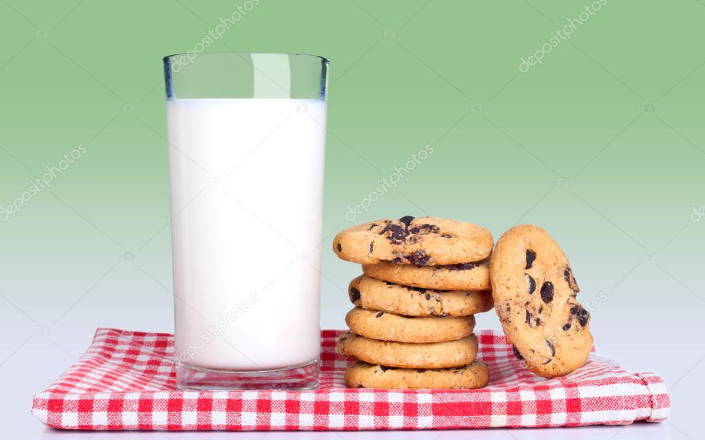 Glass of milk and cookies on kitchen towel with red cells isolated on green background  Stock Photo #16186685