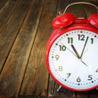 Stock Photo: Red vintage clock on wooden table