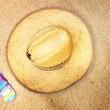 Top view of straw hat and flip flops on beach sand — Stock Photo