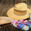 Straw hat, flip flops and cold drink on wooden background — Stock Photo