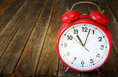 Red vintage clock on wooden table — Stock Photo