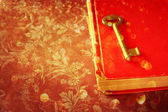 Red book and vintage key and golden glitter lights — Stock Photo