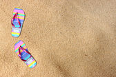 Flip flops on beach sand. room for text. — Stock Photo