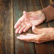 Close up of elderly male hands on wooden table — Stock Photo