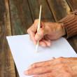 cerca de ancianas manos masculinas en mesa de madera. escrito en papel en blanco — Foto de Stock