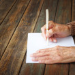 Close up of elderly male hands on wooden table . writing on blank paper — Стоковая фотография