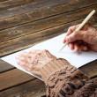 Close up of elderly male hands on wooden table . writing on blank paper — Foto de Stock