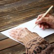 Close up of elderly male hands on wooden table . writing on blank paper — Stock fotografie
