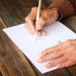 Close up of elderly male hands on wooden table . writing on blank paper — Stockfoto