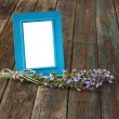 Classic blue picture frame on wooden table and sage plant decoration. — Stock Photo