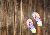 Colorful flip flops on wooden deck. summer background — Stock Photo