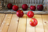 Apples in a basket on a wooden background — Stock Photo