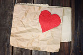 Red heart on a crumpled brown paper on wooden background — Stock Photo