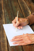 Close up of elderly male hands on wooden table . writing on blank paper — Zdjęcie stockowe