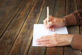 Close up of elderly male hands on wooden table . writing on blank paper — Стоковое фото