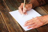 Close up of elderly male hands on wooden table . writing on blank paper — Stock Photo