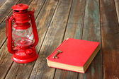 Red vintage lamp and red antique book on wooden table. vintage still life design. — Stock Photo