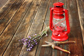 Red vintage kerosene lamp, sage and rosemary on wooden table. fine art concept. — Stock Photo