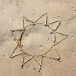 Simple sun drawn on sand of the beach — Stock Photo #29284941