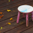 Old Wooden Stool with autumn leaves — Stock Photo