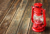 Red vintage lamp on wooden table — Stock Photo