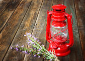 Red vintage kerosene lamp, and sage flowers on wooden table. fine art concept. — Stock Photo