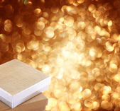 Christmas gift box on background of defocused golden lights. — Stock Photo