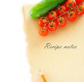Legumes frescos em um fundo de madeira e papel para anotações. — Foto Stock
