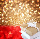 Christmas Gift over red and golden lights background — Stock Photo