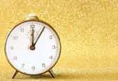 Vintage clock with glittering golden background — Stock Photo