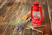 Lâmpada de querosene vintage vermelho, sálvia e alecrim na mesa de madeira. conceito de arte. — Fotografia Stock