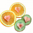 Orange and kiwi fruits with heart shapes — Stock Photo