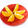 Sliced orange on red plate — Stock Photo