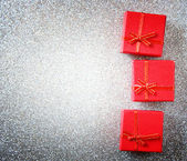 Red gift boxes on glittersilver background — Foto Stock