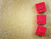Red gift boxes on glitter gold background — Stock Photo