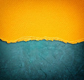 Yellow torn paper over blue background — Stock Photo