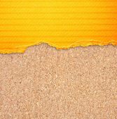 Yellow torn paper with stripes over cork board background. — Stock Photo