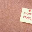 "Cork board with pinned yellow note and the phrase ""dont panic"" — Stock Photo"
