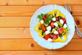 Salad with mozzarella and fresh vegetables on wooden table background. — Stockfoto