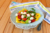 Salad with mozzarella and fresh vegetables on wooden table background. — ストック写真