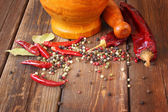 Mortar and pestle with red hot peppers and bay leaf — Stock Photo