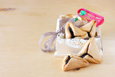 Hamantaschen cookies or hamans ears for Purim celebration in wooden box and Noisemaker — Stock Photo