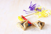 Hamantaschen cookies or hamans ears for Purim celebration and noisemaker over textured wooden board — Stock Photo