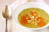 Chicken soup with carrots over white wooden textured background — Стоковое фото