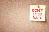 The phrase don't look back written on sticky note. room for text — Stock Photo