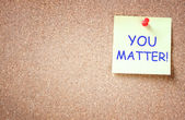 Sticky note pinned to cork board with the phrase you matter. — Stock Photo