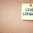 Live longer concept. memo note pinned to cork board. room for text. — Stock Photo