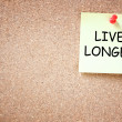 Live longer concept. memo note pinned to cork board. room for text. — Stock Photo #40947381